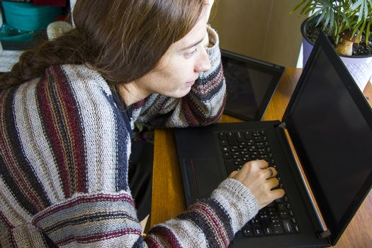 Woman working with notebook in workplace, digital tablet, mobile phone, coffee and plants in workspace, home working