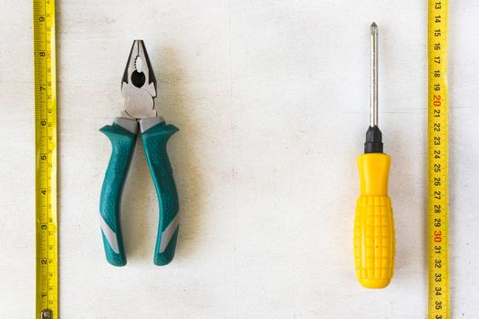 Tape measure and pliers on the white background, building instruments