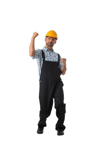Mature contractor worker in coveralls and hardhat holding fists isolated on white background full length studio portrait