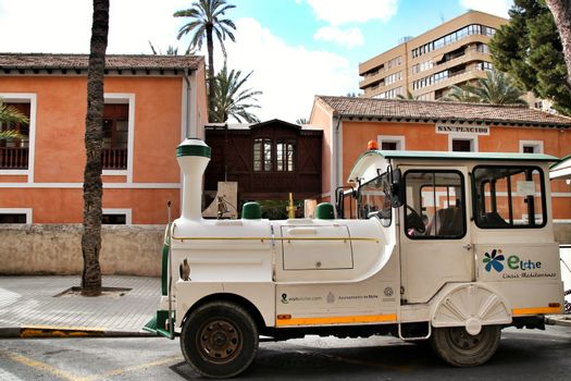 Elche, Alicante, Spain- February 14, 2019: Guided tour on Tourist train through the streets and palm groves in winter under blue sky