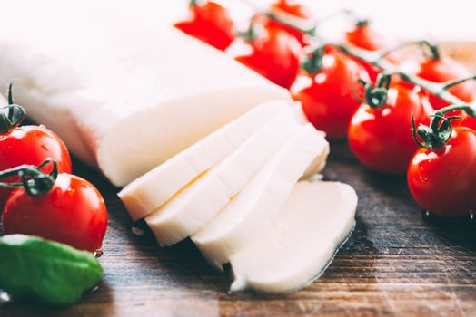 Mozzarella, cherry tomatoes and basil leaves on wooden cutting board close up