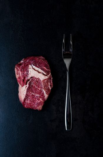 Top view on stone with steak and fork