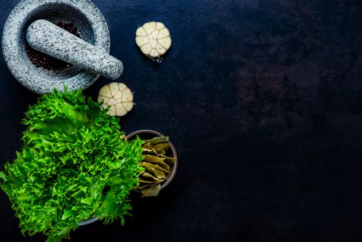 Stone mortar bowl and pestle with garlic, bay and salad leaves