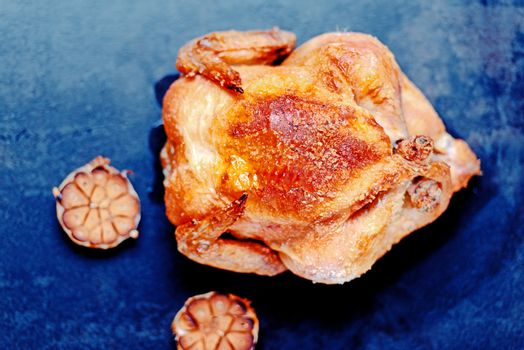Whole oven roasted chicken with garlic on stone surface