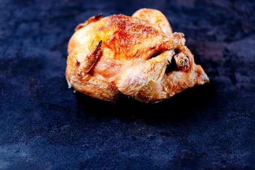 Whole oven roasted chicken on stone surface