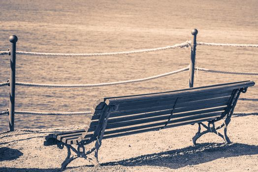 Empty bench on the beach. Concept of loneliness, emptiness, solitude.