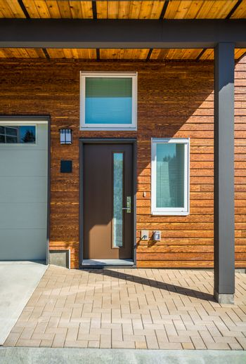 Entrance of brand new townhouse with wood siding.