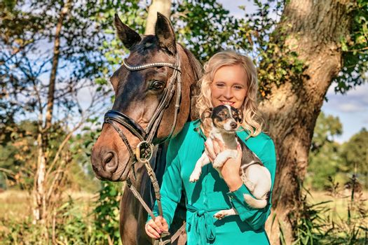 Beautiful portrait of a blond smiling girl with her horse and dog in the forest. Wearing a green dress. Selective focus.