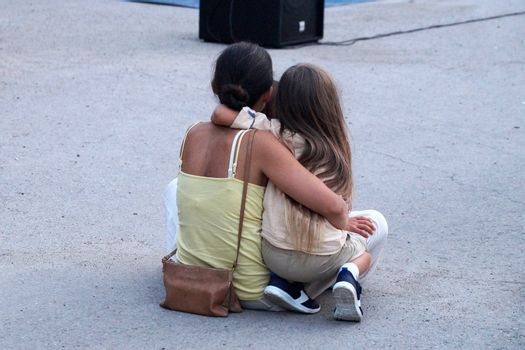 Varna, Bulgaria - 13, September, 2020: mom and daughter are hugging on the pavement, rear view