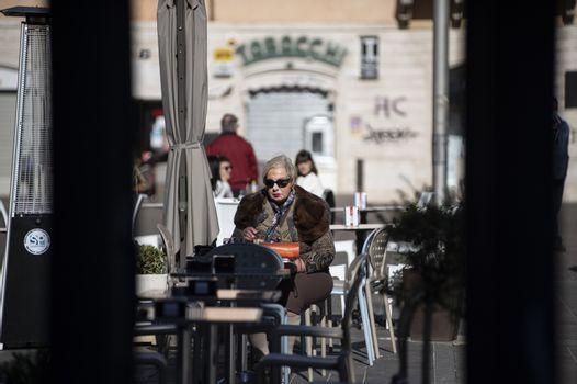 terni,italy october 21 2020:woman sitting at a table in an outdoor cafe