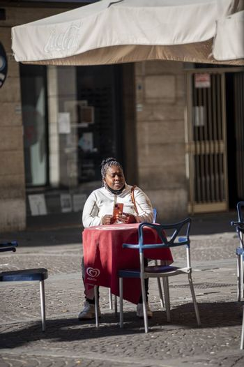 terni,italy october 21 2020:black woman sitting at a table in an outdoor cafe