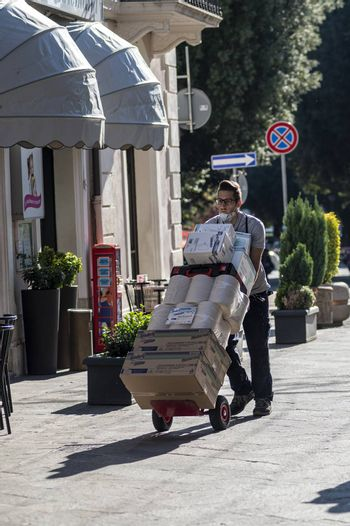 terni,italy october 21 2020:courier carrying packages in a shop