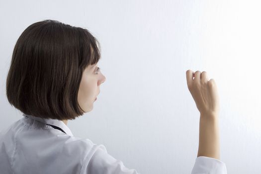 Female medical student with chalk in hand on white background