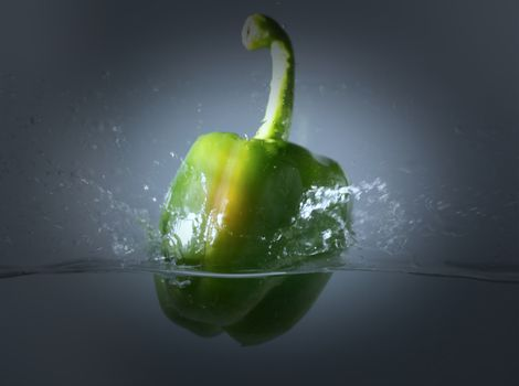 Vintage green bell peppers thrown into the water with a splash of water.