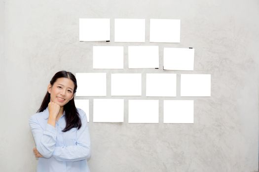 Beautiful asian young woman standing with picture gallery copy space on wall texture cement background.