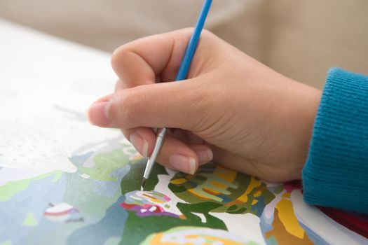 4 - A young and youthful hand holds a brush and paints by numbers