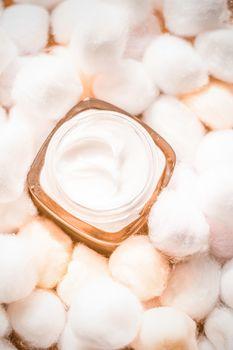 Luxury face cream for sensitive skin and orange cotton balls on