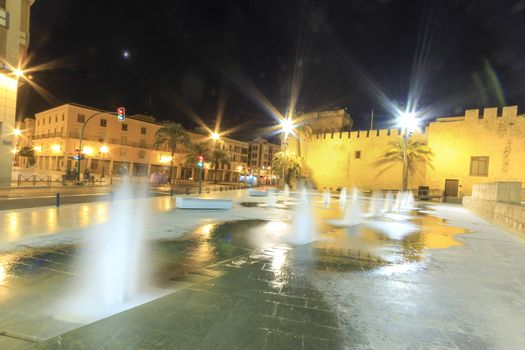 Elche, Alicante, Spain- October 22, 2020:Beautiful illuminated Altamira Palace and fountain in empty street at night in Elche, Alicante