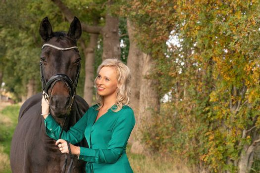 Happy beautiful girl in a green dress, cuddling her horse outdoors. Selective focus on the horse, autumn colors. fairytales background.