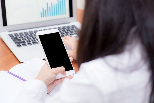 Asian woman hand holding a white phone with screen above on desk, girl using mobile with laptop, communication online digital concept.