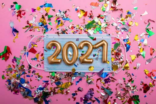 Gold numbers 2021 on face mask, pink background and confetti. Happy new pandemic year