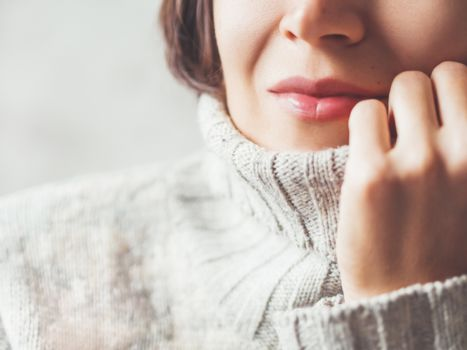 Close up portrait of woman snuggling in warm grey sweater. Casual outfit for cold weather at winter season.