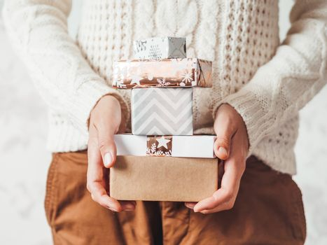 Woman in cable-knit white sweater with Scandinavian pattern and brown chinos trousers with leather belt. Stack of Christmas presents in hands. Casual outfit for New Year celebration.