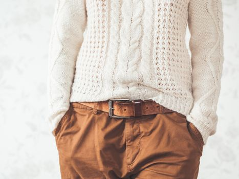 Woman in cable-knit white sweater with Scandinavian pattern and brown chinos trousers with leather belt. Casual clothes for snuggle weather. Modern urban fashion.