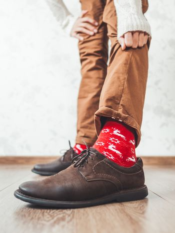 Young man pulls up leg of his chinos trousers to show bright red socks with reindeers on them. Scandinavian pattern. Winter holiday spirit. Casual outfit for New Year and Christmas celebration.