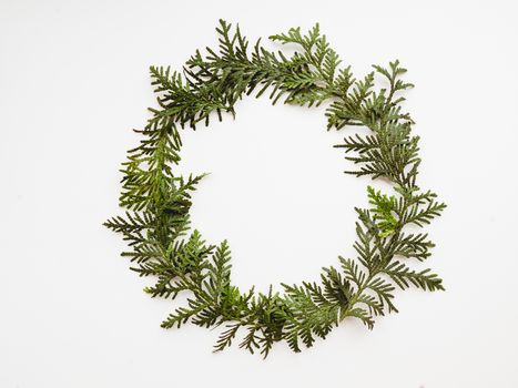 Circle wreath of twigs of thuja. Symbol of Christmas celebration and winter holiday spirit. New Year white background. Festive backdrop with copy space.
