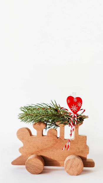 Wooden train with tied fir tree branches and red heart decoration. Cute symbol of Christmas tree brought home for New Year celebration. Winter holiday spirit. Copy space on white background.
