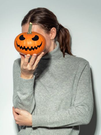 Crop unrecognizable woman holding halloween scary face bright orange pumpkin in front of her face. Young woman in gray cashemere sweater hides her face behind jack-o-lantern pumpkin. Snapshot style