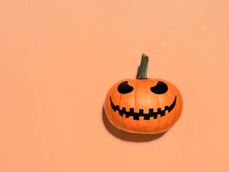 Halloween pumpkin on orange background. Halloween concept with copy space for text or design. Hard light. Jack-o-lantern laughing face on bright orange squash