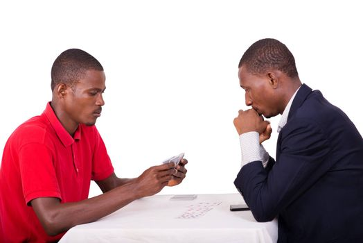 businessman playing cards with his friend around a table. man in cos sweats hands on thinking strongly to win