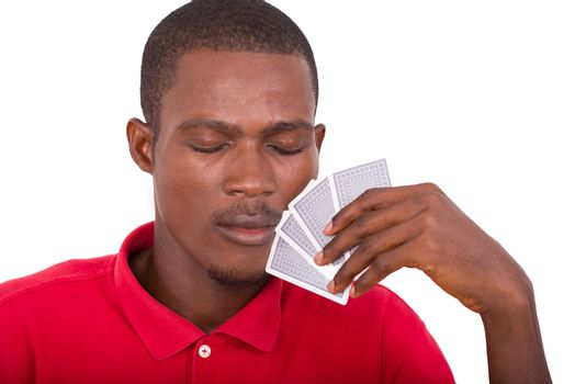 Man with his eyes closed holds in poker cards on white background