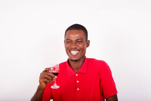 portrait of happy young standing man holding a glass of red wine isolated on a white background.
