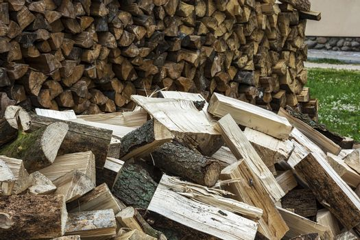 Big pile of split logs piled in a heap near the woodpile