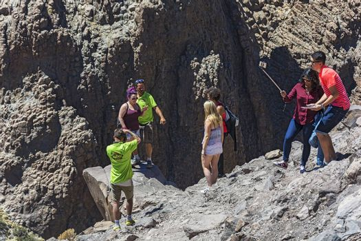 Spain, Tenerife - September 15, 2016: a group of tourists take selfies and take pictures on the mountain near the edge of the abyss
