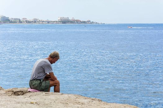 Spain, Tenerife-September 11, 2016: an Elderly man sitting on the rocks by the sea and looking down from the cliff