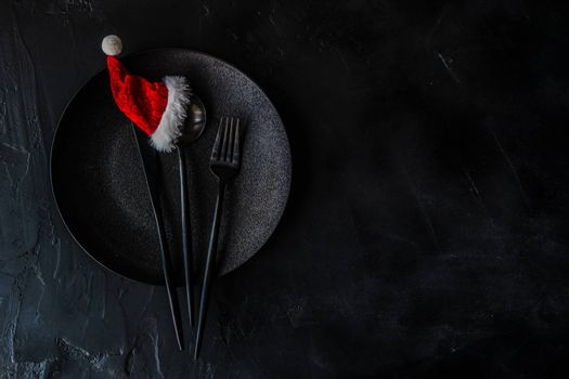 Black minimalistic cutlery set with same color cutlery and plate decorated with Santa hat