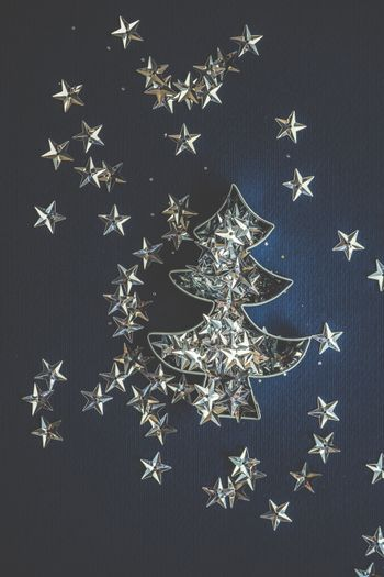 Sparkling star shaped decor on deep blue background as a Christmas card concept