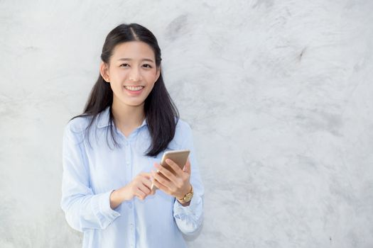 Beautiful young asian woman talking phone and smile standing on cement background, freelancer female calling telephone, communication concept.