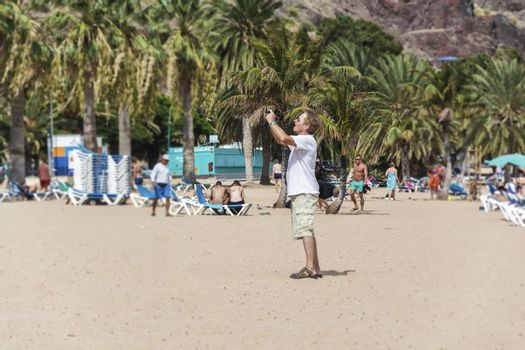 Spain, Tenerife - September 12, 2016: Man standing on the beach and taking pictures on smartphone