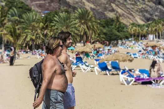 Spain, Tenerife - September 12, 2016 Two men go to the beach to swim and sunbathe