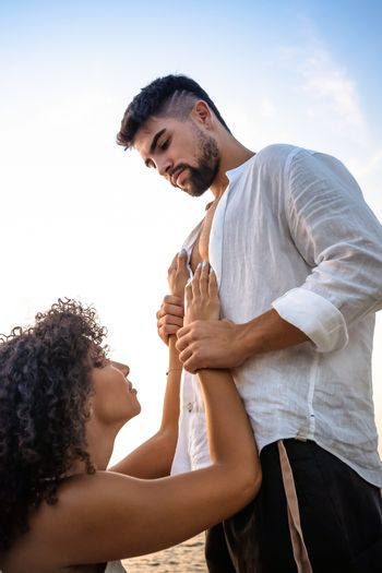 Kneeling submissive woman begs her man by holding his hands on his massive chest, but he squeezes her wrists as a sign of possession and domination - Multiracial lovers couple romance scene
