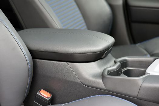 Armrest in the luxury passenger car between the front seats