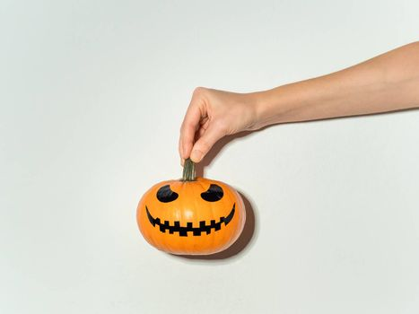 Hand holds bright orange halloween pumpkin on white wall background. Halloween concept with copy space for text or design. Hard light. Jack-o-lantern laughing face on orange squash