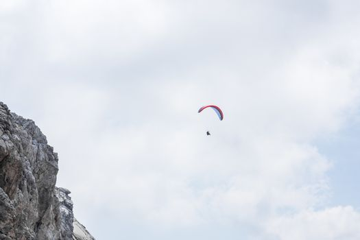 Floating paraglider on a rock face in the mountains