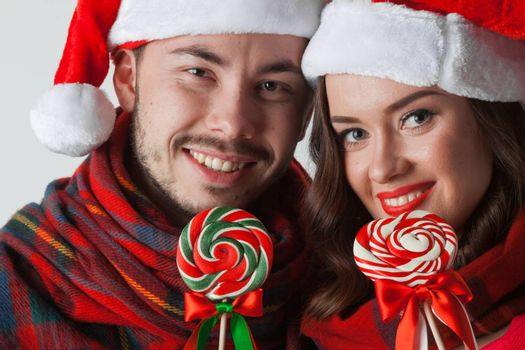 Young happy smiling couple in christmas santa hats with lollipops