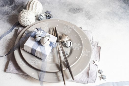 Festive Christmas card concept with table setting in grey monochrome with star shaped decor on concrete background with copy space